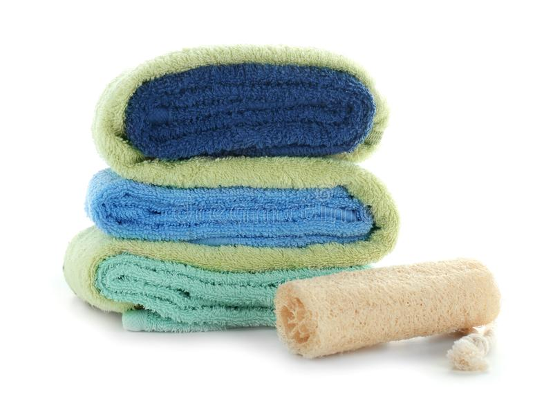 Stack of clean soft towels with bath wisp on white background stock image