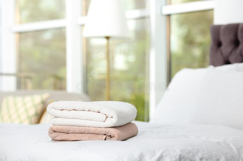 Stack of clean terry towels on bed. Space for text royalty free stock photo