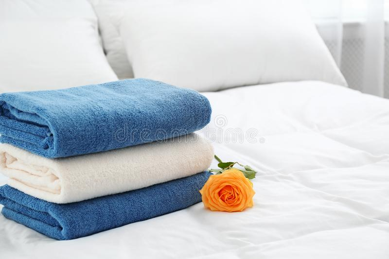 Stack of clean towels and beautiful rose flower on bed. Space for text stock photos