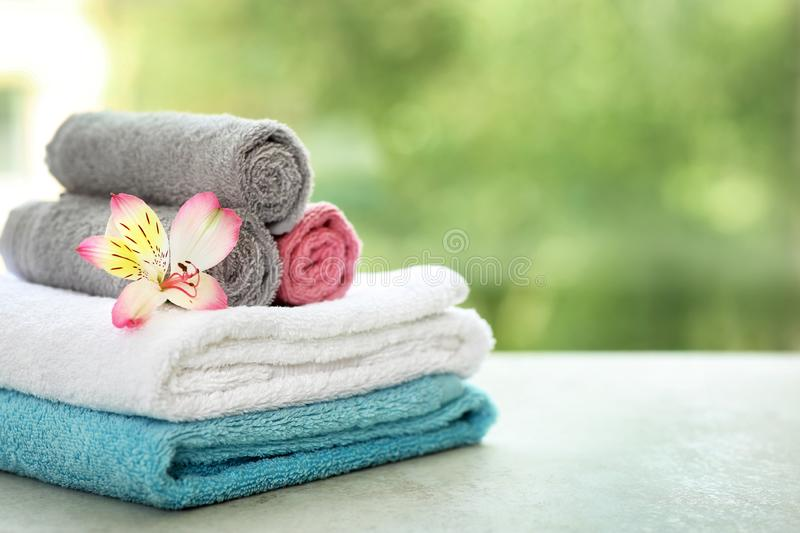 Stack of clean towels with flower on table against blurred background. Space for text royalty free stock photography