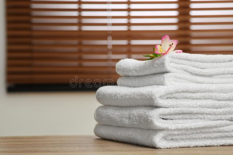 Stack of clean towels with flower on table indoors. Space for text royalty free stock image