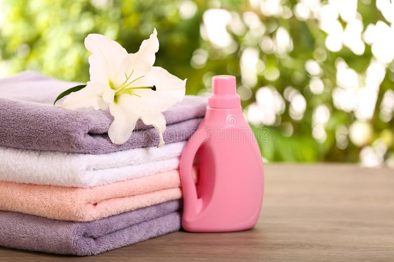 Stack of clean towels with lily and detergent on table against blurred background. Space for text royalty free stock photo