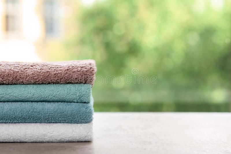 Stack of clean towels on table against blurred background. Space for text stock photo