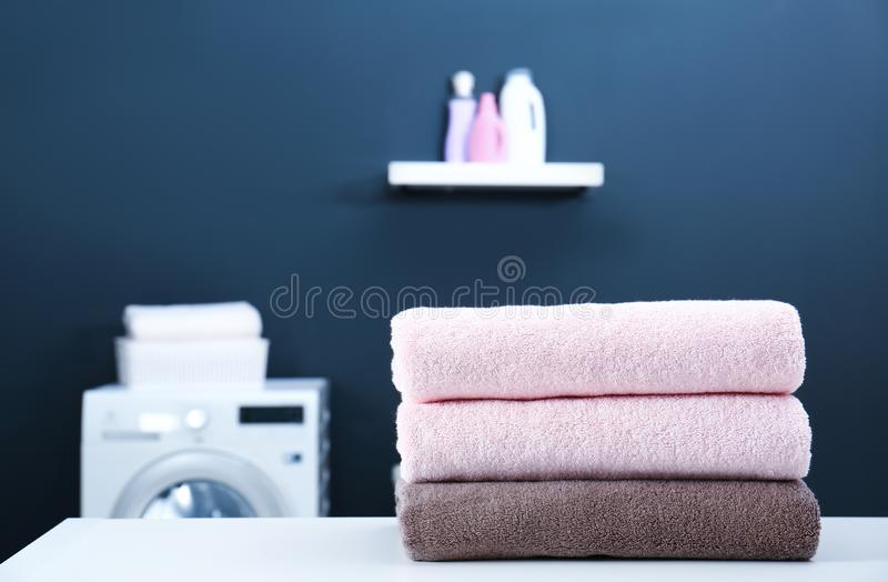 Stack of clean towels on table in laundry roomt. Stack of clean towels on table in laundry room. Space for text stock photos
