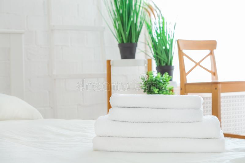 Stack of clean towels on white bed in room. Space for text stock photo
