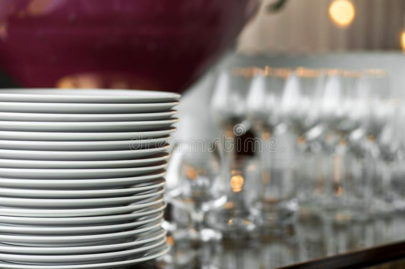 A stack of clean white plates stands on a table with a white tablecloth in an indoor restaurant. Buffet at the party. Blank empty. Glasses on the background royalty free stock images