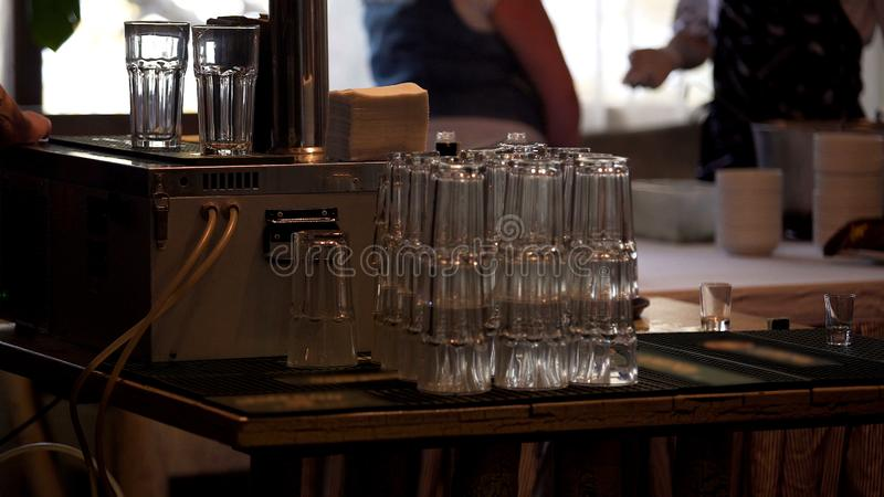 Stack of cleaned glasses on bar counter, catering service at company party stock photo