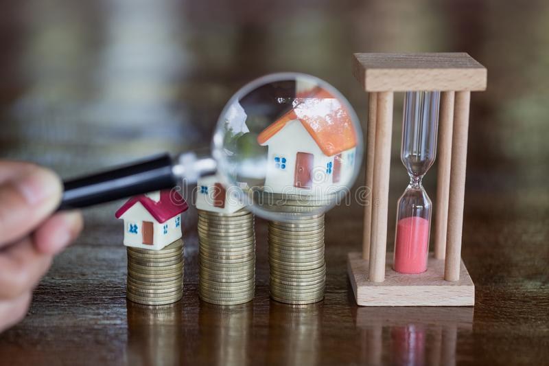 Stack coin and bar graph with grow, magnifying glass searching for a new home, Loan for real estate or save money for buy a house stock images