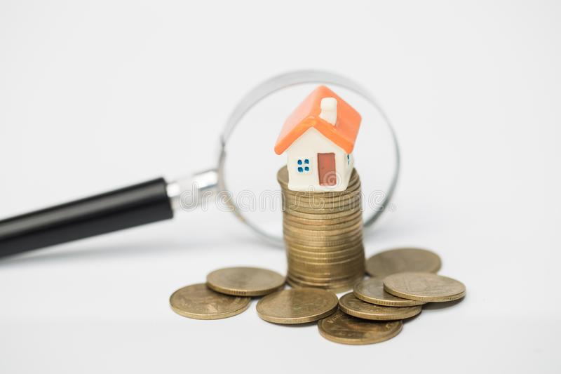 Stack coin with grow, magnifying glass searching for a new home, Loan for real estate or save money for buy a house to family in. The future concept stock photos