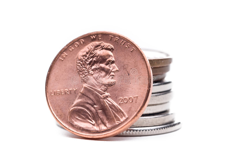 A stack of coins. A US copper penny against a stack of coins stock photos