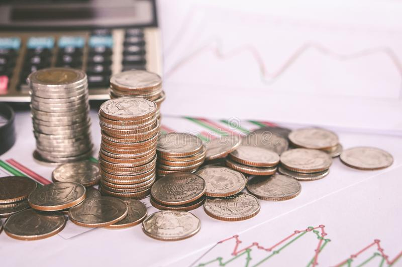 Stack of coins, calculator and stock chart report, business and finance concept. Closeup stack of coins, calculator and stock chart report, business and finance royalty free stock photos