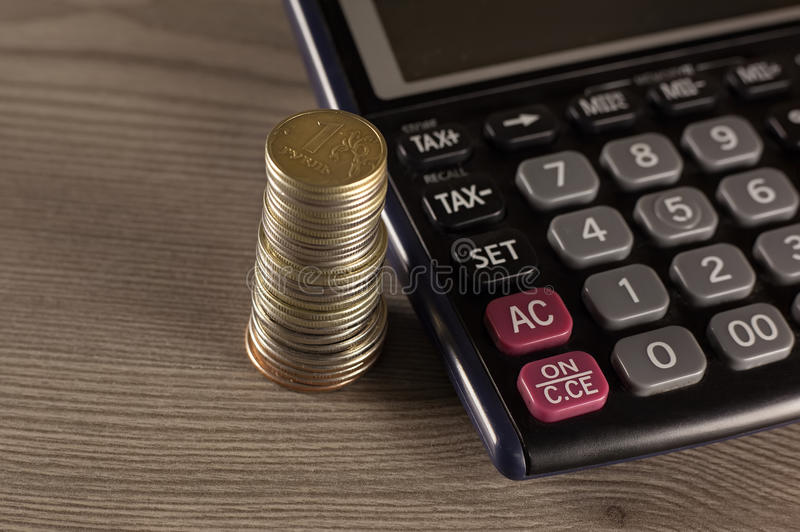 Stack of coins and calculator royalty free stock photography