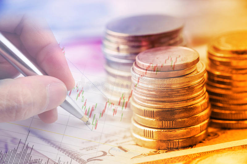 Stack of coins and a hand holding a ballpoint pen is examining a technical chart of financial instrument. stock photography