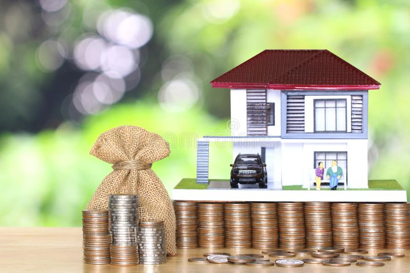 Stack of coins money and bag with model house and miniature couple on natural green background, Save money for prepare in future. And retirement concept stock photos