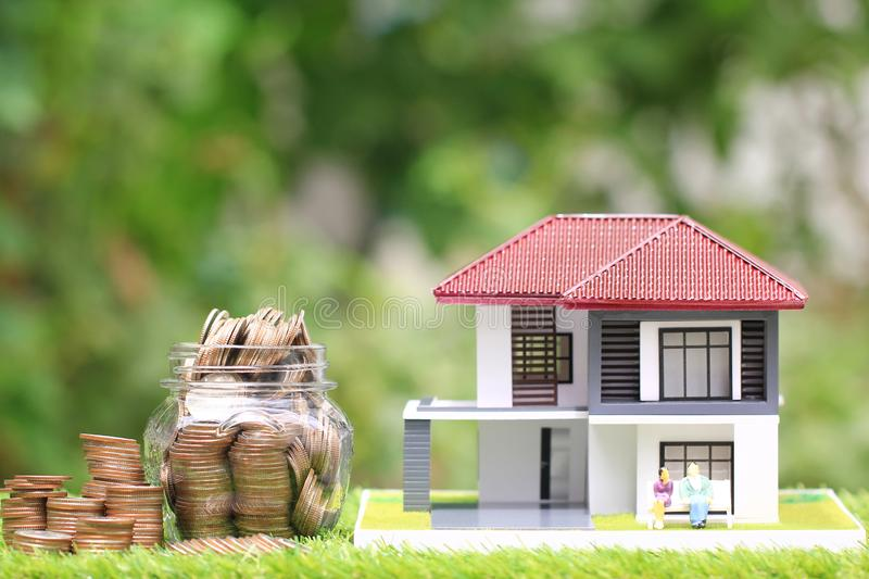 Stack of coins money in glass bottle with model house and miniature couple on natural green background, Save money for prepare in. Future and retirement concept royalty free stock photography