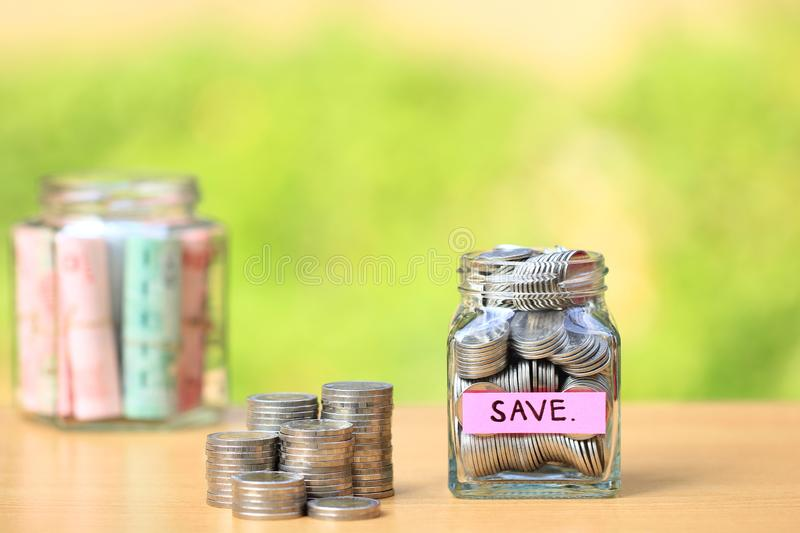 Stack of coins money and the glass bottle on natural green background, Business investment growth and save money for prepare in. Future concept stock photo