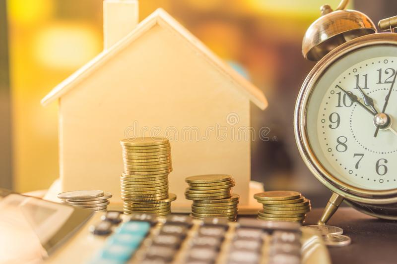 Stack of coins planing to buy home with clock and house model stock photography