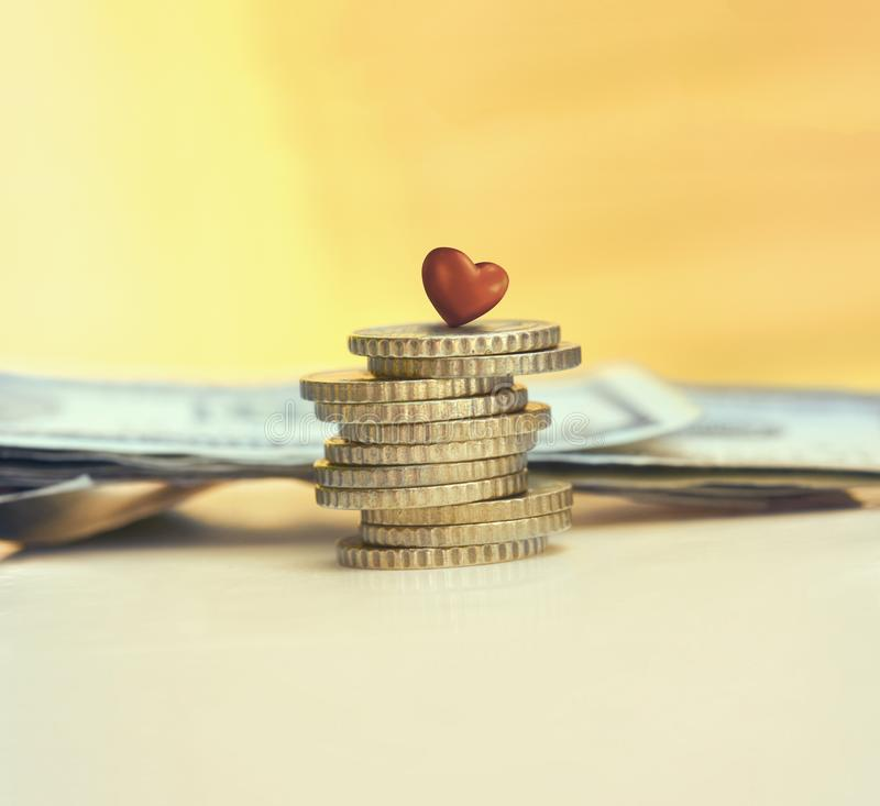 Stack of coins with red heart. Money saving, charity and healthcare concept. A stack of coins with red heart stock photo