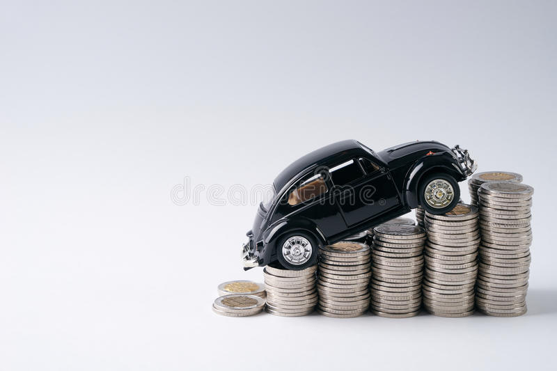 Stack of coins. A toy black car model in top of stack of coins isolated on white background with copy space.Financial and business concept stock photo