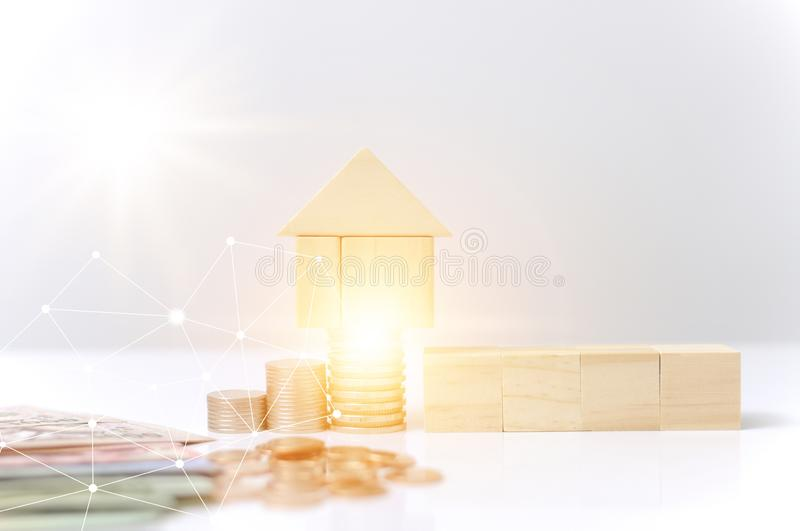 Stack coins,wooden blocks house with light effect graphic for internet of thing link communication technology saving to. Stack coins,wooden blocks house with royalty free stock image