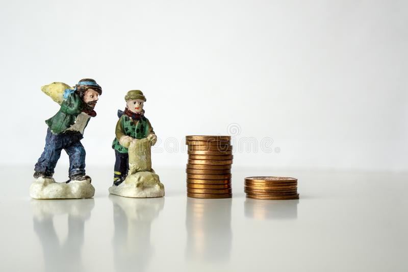 Stack of coins with worker figures on white background Working for pennies concept Low salary stock photo