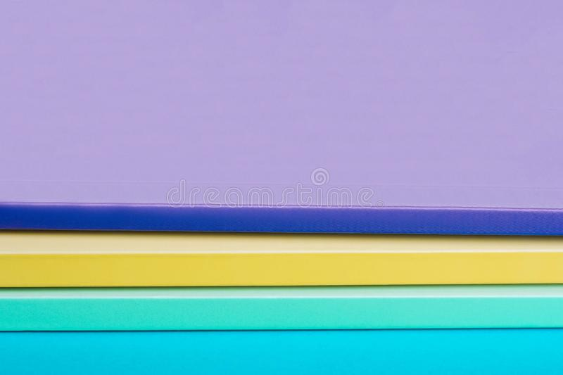 Stack of color notebooks, yellow, purple, green stock photos