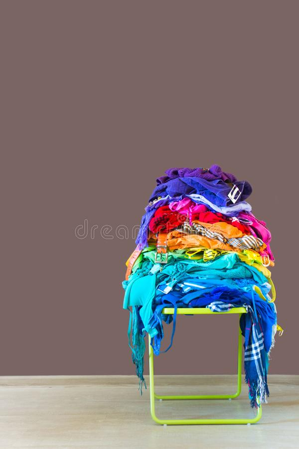 A stack of colored things on a chair. Cluttering of clothes. Cleaning in the closet. Clothes stacked in a bunch of flowers. Women`s wardrobe. Many things royalty free stock photography