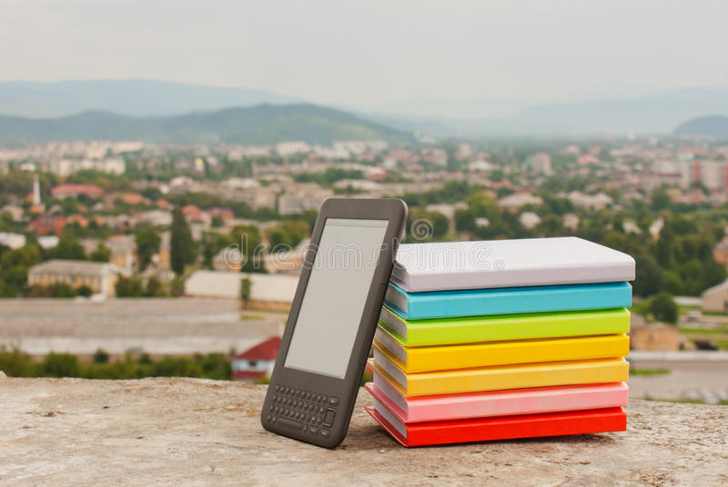 Stack of colorful books with e-book reade stock photo