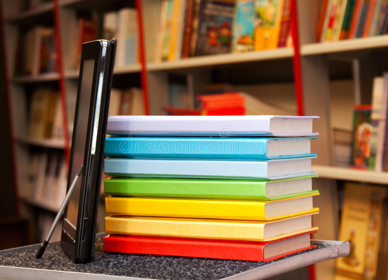 Stack of colorful books with e-book reader stock image