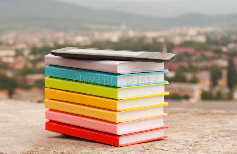 Stack of colorful books with electronic book reade stock photos