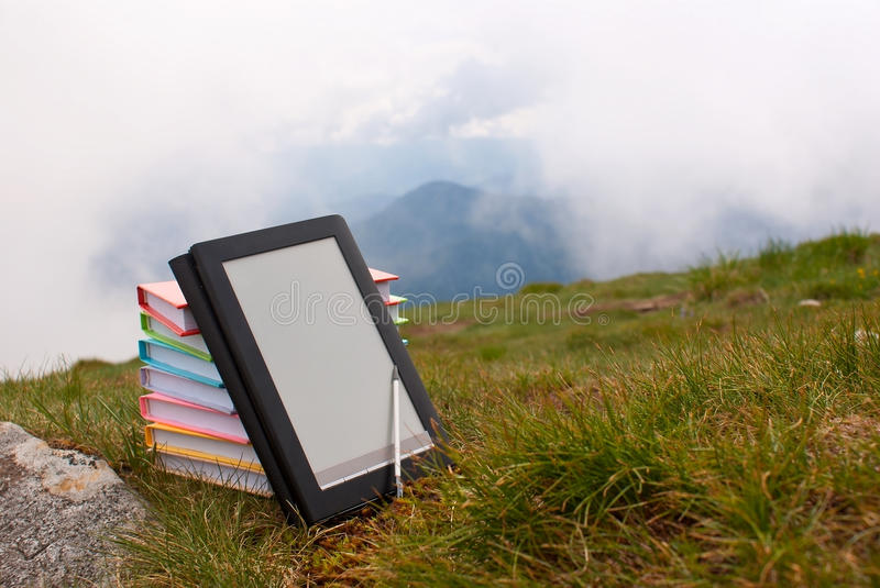 Stack of colorful books and electronic book reader. On the grass stock image