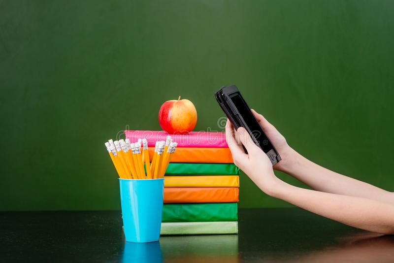 Stack of colorful books with electronic book reader near empty green chalkboard. Sample for text royalty free stock photos
