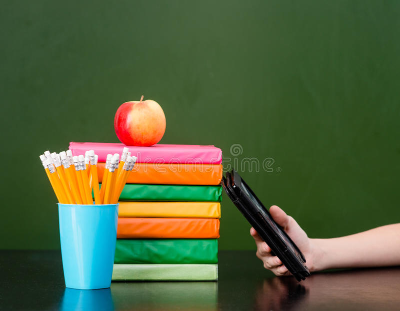 Stack of colorful books with electronic book reader near empty green chalkboard. Sample for text royalty free stock photography