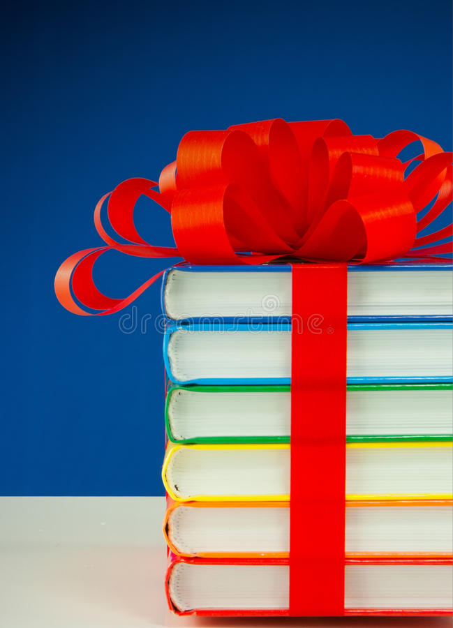 Stack of colorful books tied up with a red ribbon royalty free stock photography