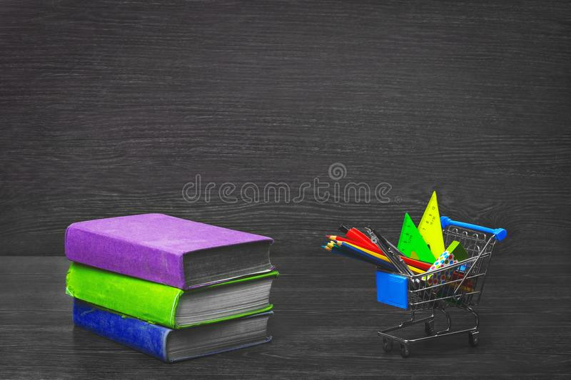 Stack of colorful books on a wooden table, and grocery cart with stationery. royalty free stock photos
