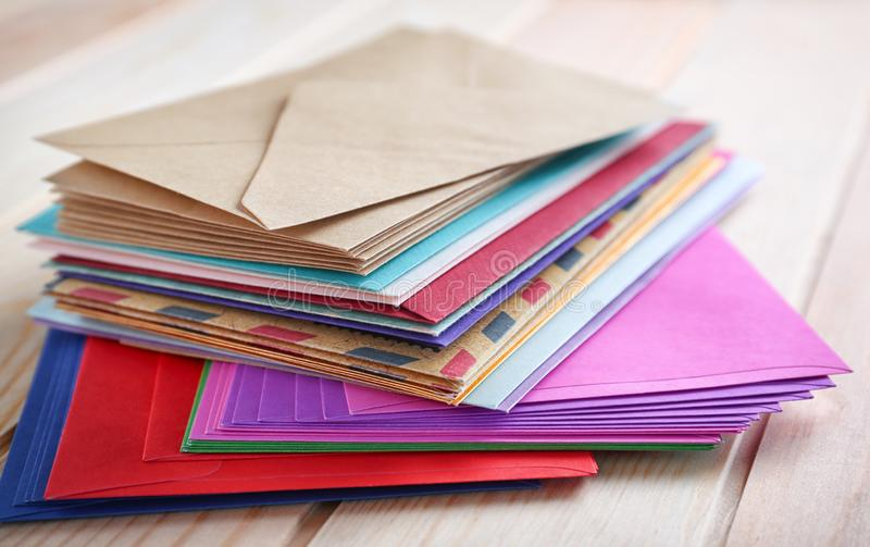 Stack of colorful envelopes on wooden table, closeup. Mail service royalty free stock photo