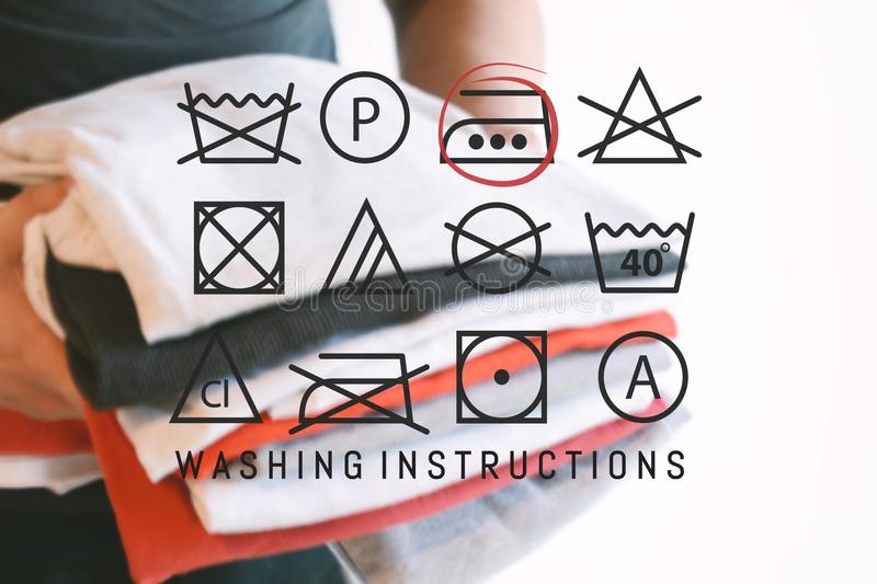 Stack of colorful folded shirts with laundry instructions symbol stock image