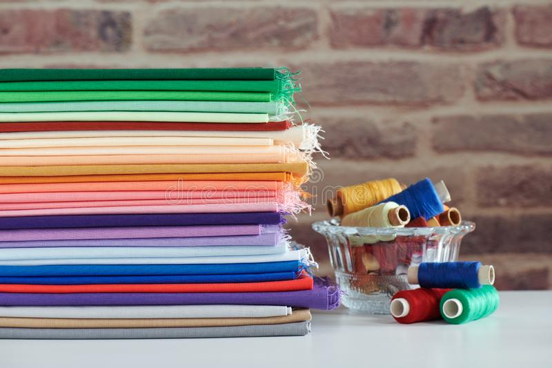 Stack of colorful monochromatic fabrics and spools of thread on brick wall background stock photo
