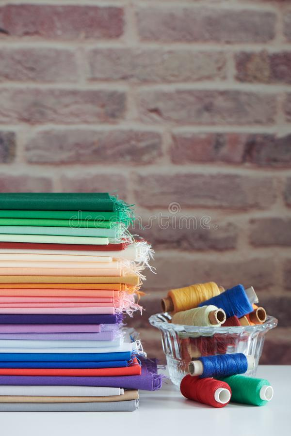 Stack of colorful monochromatic fabrics and spools of thread on brick wall background, space for text royalty free stock photos
