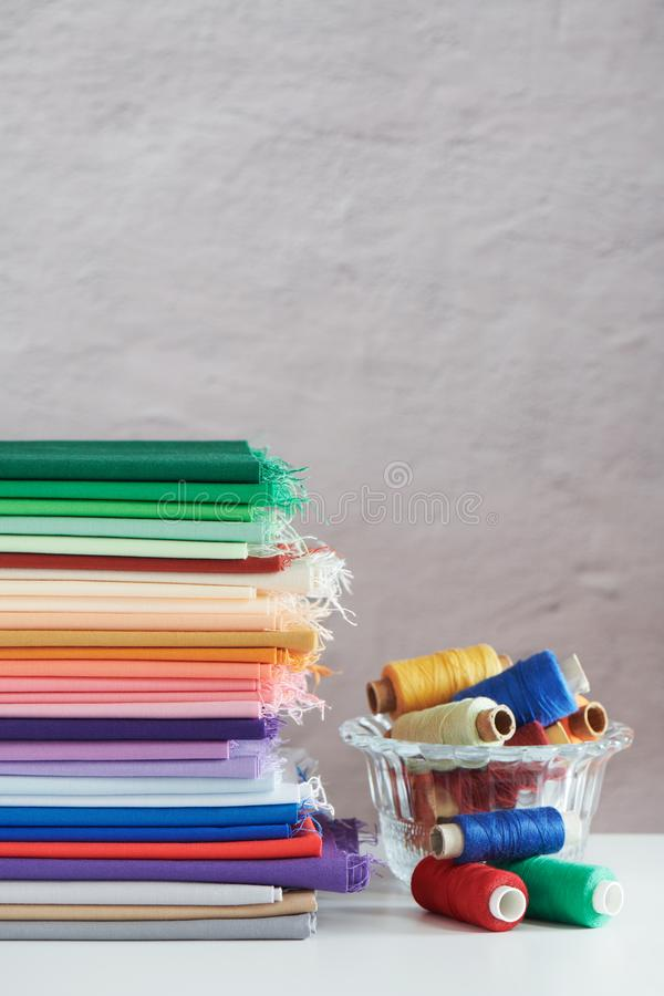 Stack of colorful monochromatic fabrics and spools of thread on grey  background, space for text royalty free stock photos