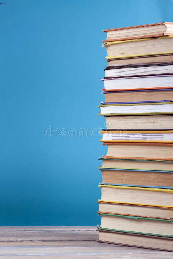 Stack of colorful real books on blue background, partial view. Back to school. Copy Space. Education background. royalty free stock photos