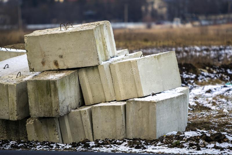 Stack of concrete blocks for foundation on construction site. Ferroconcrete reinforced with metal blocks stock photography
