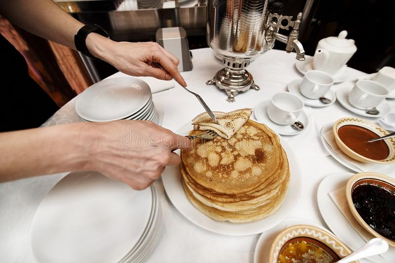 A stack of cooked pancakes in a white plate stand on a serivirovannom table with a samovar. Girl a fork and a knife takes a pancake. & A Stack Of Cooked Pancakes In A White Plate Stand On A ...