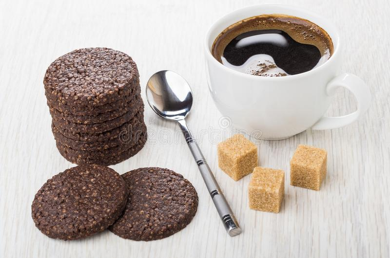 Stack of cookies with airy rice, chocolate, spoon, sugar, coffee. Stack of cookies with airy rice and chocolate, spoon, sugar cubes, coffee in cup on wooden royalty free stock photos