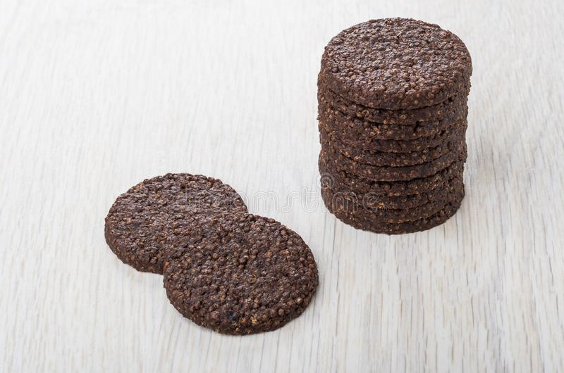 Stack of cookies with airy rice and chocolate on table. Stack of cookies with airy rice and chocolate on light wooden table stock photos
