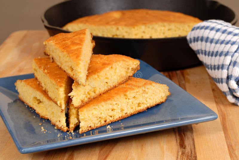Stack of cornbread on plate. A stack of cornbread on a blue plate with skillet in background royalty free stock images
