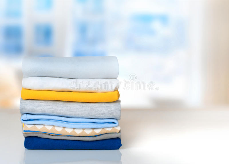 Stack cotton folded clothes on table indoors empty space. royalty free stock photos