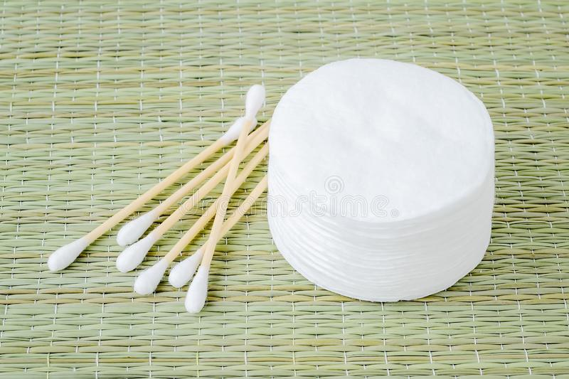 Stack of cotton pads and heap of wood stick cotton buds on a background of rough wicker mat made of bast fibers. Plastic free. Hygiene supplies, beauty tools stock image