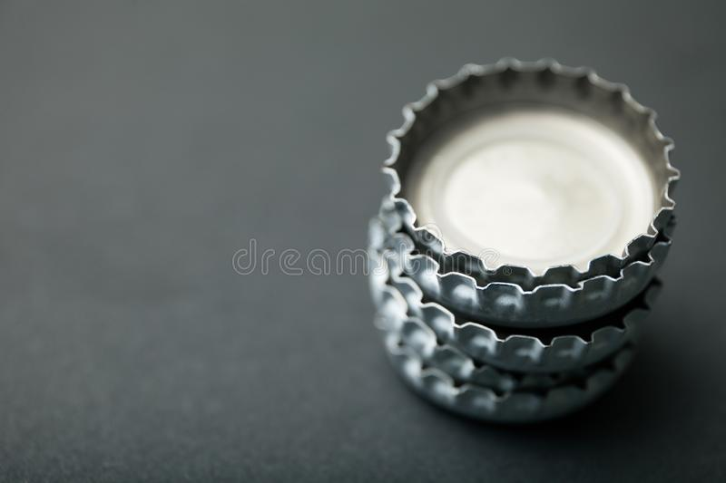 Stack of covers from beer bottles, empty space for text stock image