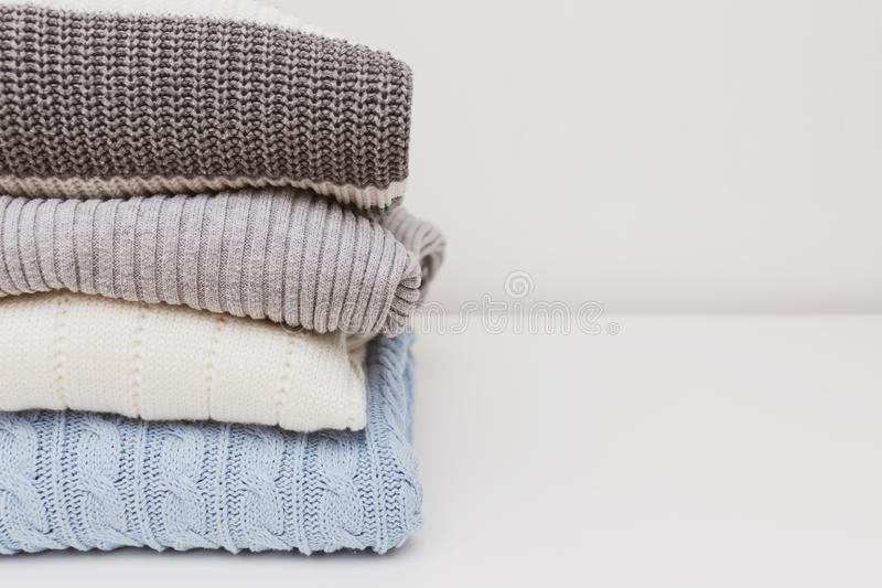 Stack of cozy comfortable homely knitted sweaters in pastel colors, cosy homelike clothes concept with copy space stock image